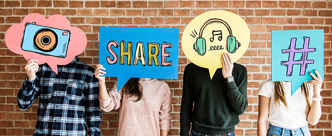 Four people stand next to each other holding sings with different symbols relating to social media above their heads.