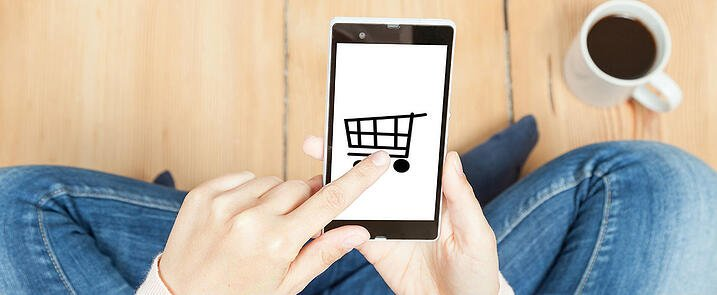 Someone is opening an App with a shopping cart logo on a smartphone.