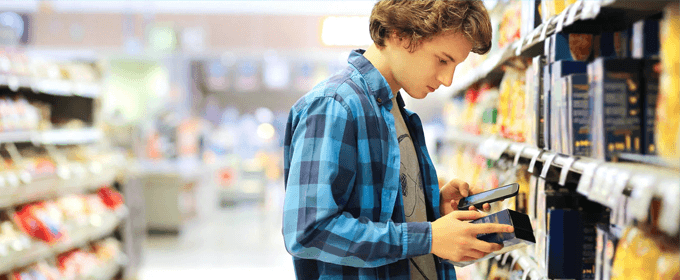 young man using smartphone to research product in the store