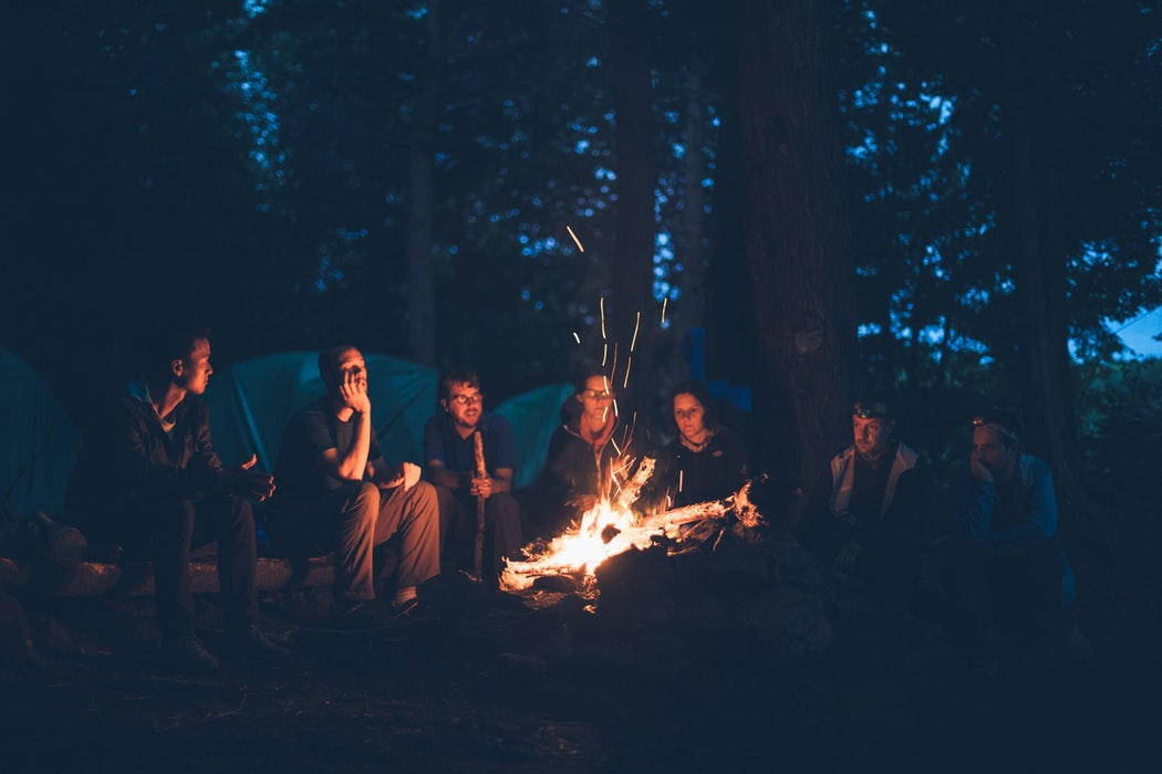 people sitting around a camp fire